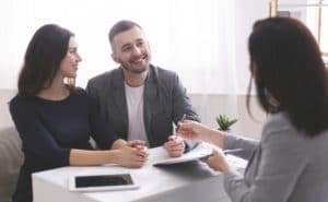 Young family listening to financial advisor, ready to sign credit contract